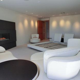 Свежая идея для дизайна: хозяйская спальня среднего размера в стиле модернизм с белыми стенами, бетонным полом, горизонтальным камином, фасадом камина из металла и белым полом - отличное фото интерьера