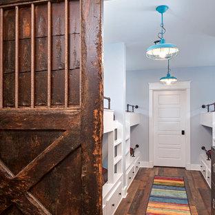 Immagine di una camera degli ospiti eclettica con pareti grigie e pavimento in legno massello medio