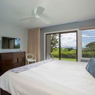 This is an example of a transitional master bedroom in Hawaii with grey walls and porcelain floors.