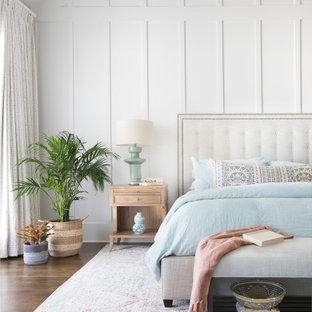 Cette image montre une grand chambre parentale marine avec un mur blanc, un sol en bois brun, un sol marron et boiseries.
