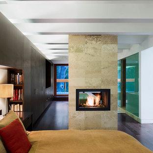 Diseño de dormitorio principal, moderno, pequeño, con paredes negras, suelo de madera oscura, chimenea de doble cara y marco de chimenea de piedra