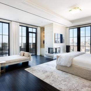 ニューヨークの広いエクレクティックスタイルのおしゃれな主寝室 (ベージュの壁、濃色無垢フローリング、コーナー設置型暖炉、石材の暖炉まわり)