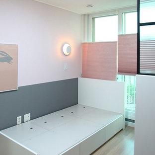 Immagine di una camera degli ospiti minimalista di medie dimensioni con pareti rosa e pavimento in bambù