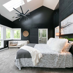 This is an example of a contemporary master bedroom in Nashville with black walls and carpet.