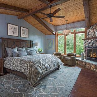 Diseño de dormitorio rural con paredes azules, suelo de madera en tonos medios, chimenea de esquina, marco de chimenea de piedra y suelo marrón