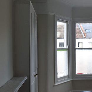 ロンドンの広いトラディショナルスタイルのおしゃれな主寝室 (緑の壁、カーペット敷き、標準型暖炉、石材の暖炉まわり、緑の床、折り上げ天井、壁紙)