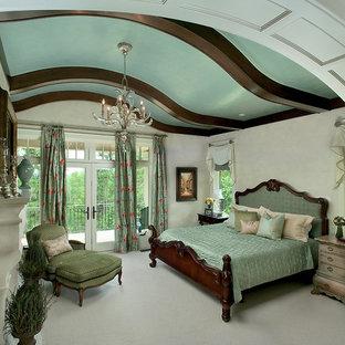 Modelo de dormitorio principal, tradicional, grande, con paredes beige, moqueta, chimenea tradicional y marco de chimenea de piedra