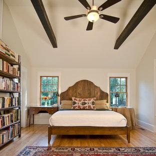 Modelo de dormitorio principal, contemporáneo, de tamaño medio, sin chimenea, con paredes blancas, suelo de madera clara y suelo marrón