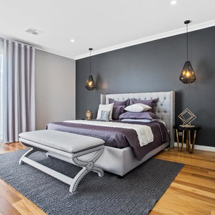 This is an example of a mid-sized contemporary bedroom in Perth with multi-coloured walls, medium hardwood floors and brown floor.