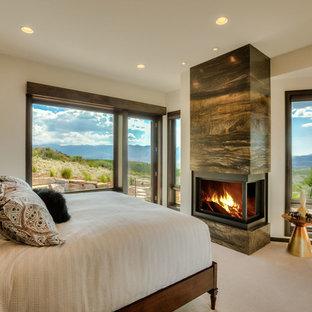 Modelo de dormitorio principal, tradicional renovado, de tamaño medio, con paredes blancas, moqueta, chimenea de doble cara, marco de chimenea de baldosas y/o azulejos y suelo blanco