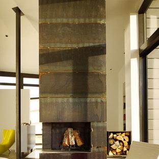 На фото: большая хозяйская спальня в стиле модернизм с белыми стенами, бетонным полом, стандартным камином и фасадом камина из металла с