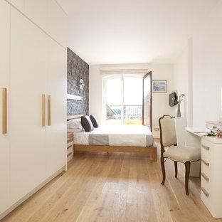 Ejemplo de dormitorio actual con paredes multicolor y suelo de madera clara