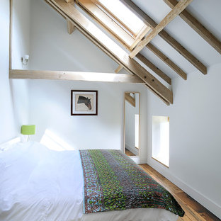 This is an example of a country bedroom in Hampshire with white walls and medium hardwood floors.