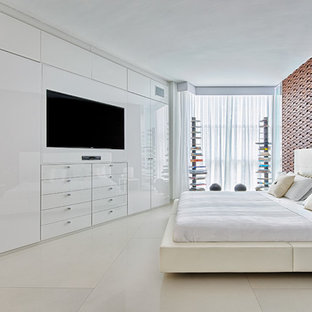This is an example of a mid-sized contemporary master bedroom in Miami with white walls and concrete floors.