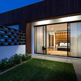 Imagen de dormitorio principal, industrial, grande, con paredes multicolor, suelo de madera en tonos medios y suelo marrón