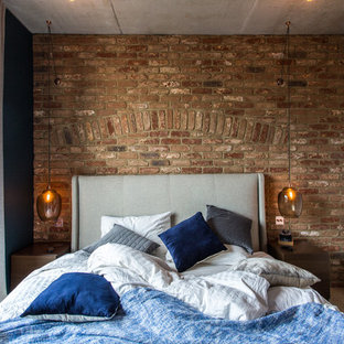 Photo of an industrial bedroom in London with blue walls, light hardwood flooring and brown floors.