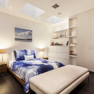This is an example of a contemporary bedroom in Melbourne with white walls, dark hardwood floors and brown floor.