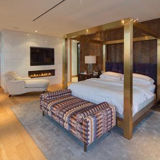 Imagen de dormitorio principal, actual, extra grande, con paredes blancas, suelo de madera clara, chimenea lineal, marco de chimenea de baldosas y/o azulejos y suelo beige