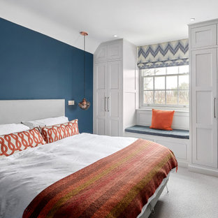 Design ideas for a medium sized traditional master bedroom in West Midlands with blue walls, carpet and grey floors.