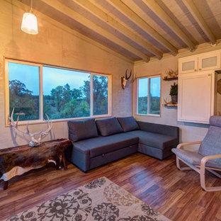 Esempio di una camera degli ospiti rustica di medie dimensioni con pareti grigie, pavimento in legno massello medio, camino sospeso e pavimento marrone