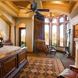 Стильный дизайн: огромная хозяйская спальня в средиземноморском стиле с бежевыми стенами, полом из травертина, стандартным камином и фасадом камина из камня - последний тренд