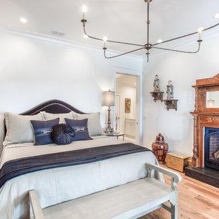 Modelo de dormitorio principal, costero, de tamaño medio, con paredes blancas, suelo de madera en tonos medios, chimenea tradicional, marco de chimenea de madera y suelo marrón