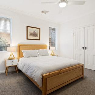 Modelo de habitación de invitados costera, de tamaño medio, con paredes blancas, moqueta y suelo gris