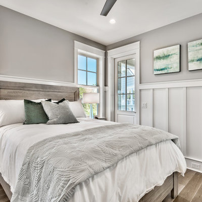 Example of a mid-sized beach style guest dark wood floor and brown floor bedroom design in Miami with gray walls and no fireplace