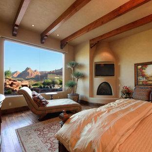 Стильный дизайн: хозяйская спальня среднего размера с бежевыми стенами, темным паркетным полом, стандартным камином и фасадом камина из штукатурки - последний тренд