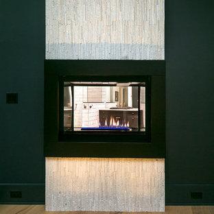 Imagen de dormitorio principal, contemporáneo, de tamaño medio, con paredes grises, suelo de madera en tonos medios, chimenea de doble cara y marco de chimenea de piedra