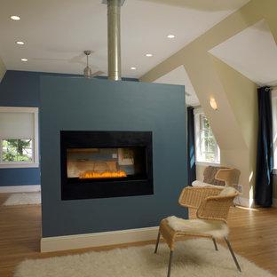 Foto de dormitorio principal, escandinavo, grande, con paredes azules, suelo de madera clara, chimenea de doble cara y marco de chimenea de yeso