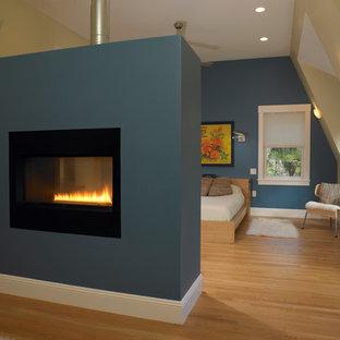 Modelo de dormitorio principal, nórdico, grande, con paredes azules, suelo de madera clara, chimenea de doble cara y marco de chimenea de yeso