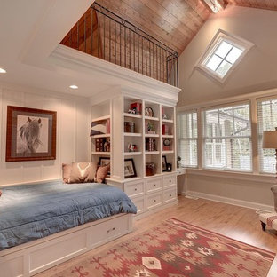 This is an example of an expansive traditional loft-style bedroom in Minneapolis with beige walls and light hardwood floors.