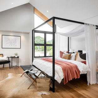 Inspiration for a contemporary bedroom in Perth with white walls, medium hardwood floors and brown floor.