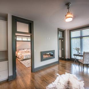 Пример оригинального дизайна: огромная хозяйская спальня в стиле современная классика с белыми стенами, паркетным полом среднего тона, горизонтальным камином и фасадом камина из штукатурки