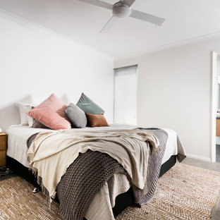 This is an example of a mid-sized beach style master bedroom in Perth with white walls, carpet, no fireplace and grey floor.