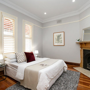This is an example of a transitional guest bedroom in Sydney with grey walls, medium hardwood floors, a corner fireplace, a wood fireplace surround and brown floor.