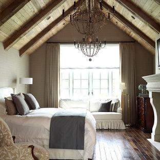 Diseño de dormitorio de estilo de casa de campo, grande, con paredes grises, suelo de madera oscura, chimenea tradicional y marco de chimenea de piedra