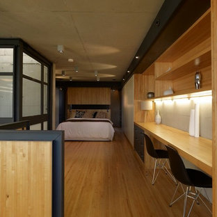 Design ideas for a mid-sized industrial loft-style bedroom in Sydney with light hardwood floors and beige floor.