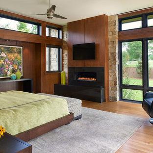 Modelo de dormitorio principal, actual, grande, con paredes marrones, suelo de madera clara, chimenea lineal y marco de chimenea de piedra
