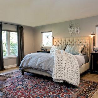 Example of an eclectic master medium tone wood floor and beige floor bedroom design in Austin with gray walls