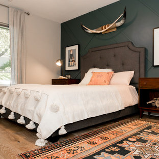 Inspiration for an eclectic guest medium tone wood floor and beige floor bedroom remodel in Austin with green walls