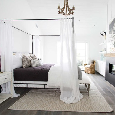 Example of a large beach style master dark wood floor bedroom design in Orange County with white walls and a ribbon fireplace