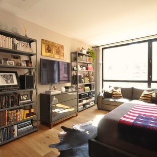 Small eclectic loft-style bedroom in New York with beige walls and light hardwood floors.