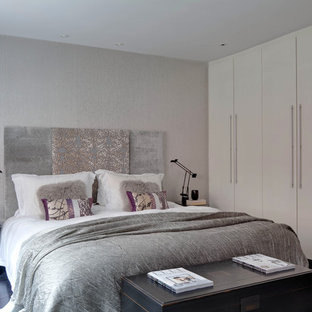 Design ideas for a small contemporary master bedroom in London with grey walls and dark hardwood flooring.