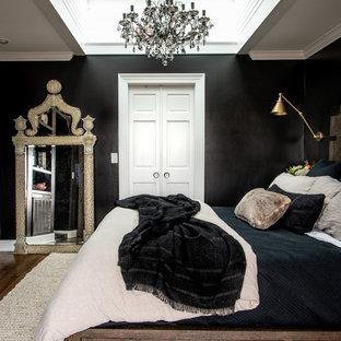 Foto di una grande camera matrimoniale tradizionale con pareti nere, parquet scuro, camino classico, cornice del camino in mattoni e pavimento marrone