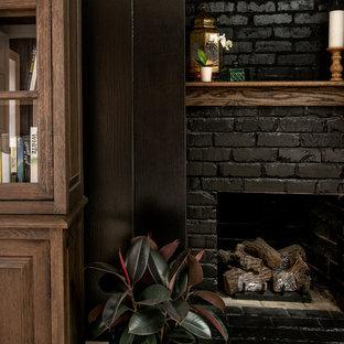 Ejemplo de dormitorio principal, clásico renovado, grande, con paredes negras, suelo de madera oscura, chimenea tradicional, marco de chimenea de ladrillo y suelo marrón