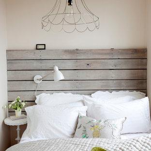 Shabby chic-inspirerad inredning av ett sovrum, med beige väggar
