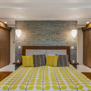 Großes Retro Hauptschlafzimmer mit bunten Wänden und braunem Holzboden in Sonstige