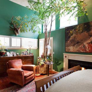 ロサンゼルスの大きいエクレクティックスタイルのおしゃれな主寝室 (緑の壁、濃色無垢フローリング、標準型暖炉、木材の暖炉まわり)
